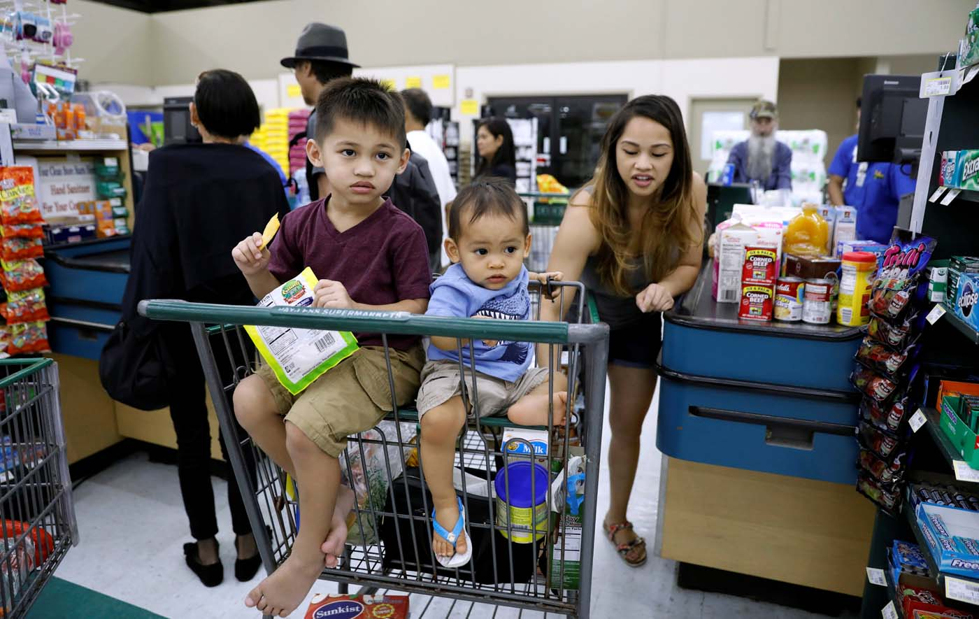 Children ride in a shopping cart, as residents shop for food supplies, at a grocery store in Dededo, Guam, a U.S. Pacific Territory, August 12, 2017. REUTERS/Erik De Castro