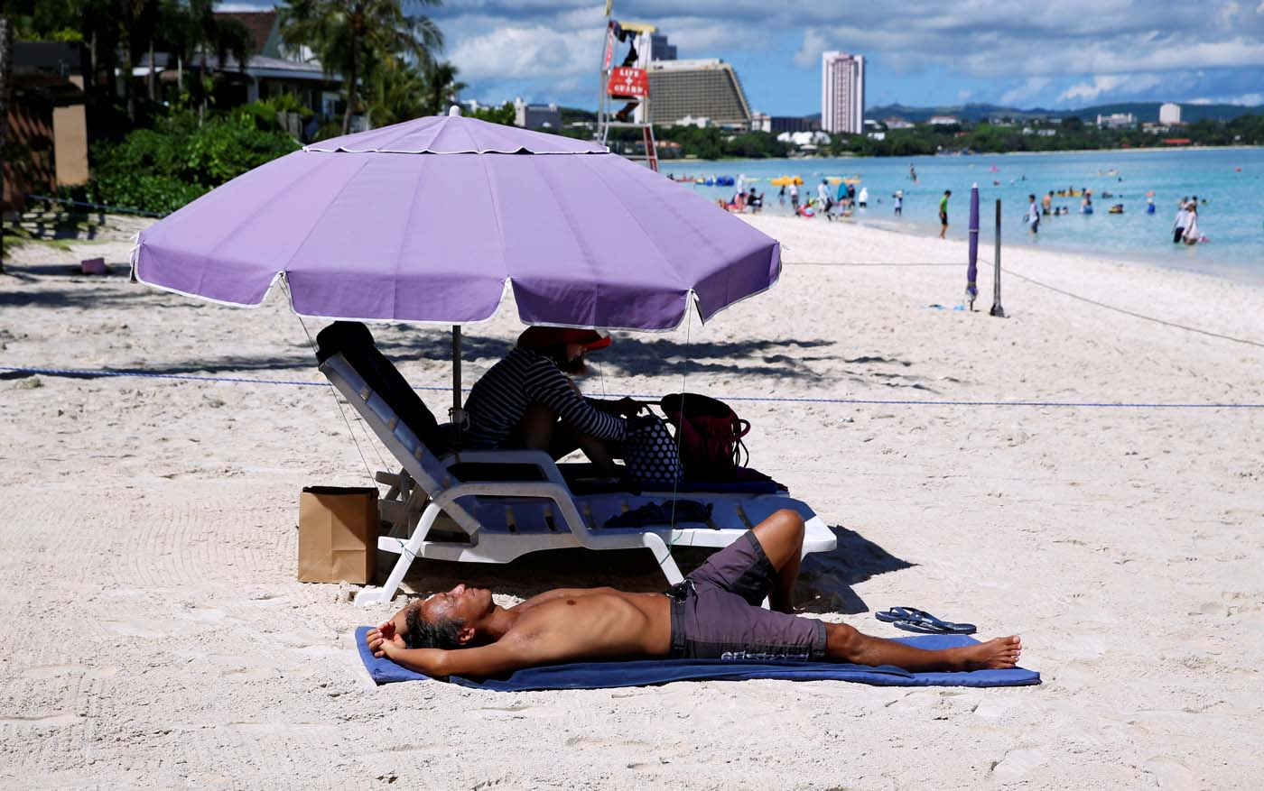 Tourists enjoy the beach in the Tumon tourist district on the island of Guam, a U.S. Pacific Territory, August 12, 2017. REUTERS/Erik De Castro