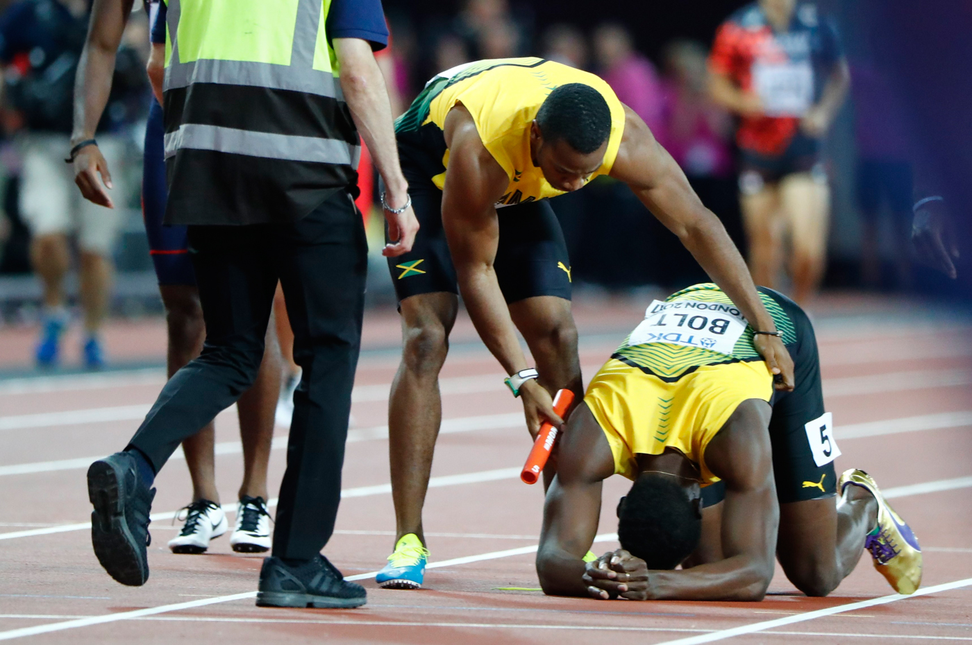 Athletics - World Athletics Championships – men's 4 x 100 meters relay final – London Stadium, London, Britain – August 12, 2017 – Usain Bolt of Jamaica is comforted by his teammate. REUTERS/Lucy Nicholson