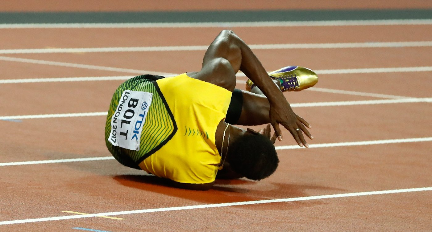 Athletics - World Athletics Championships - Men's 4x100 Metre Final - London Stadium, London, Britain – August 12, 2017. Usain Bolt of Jamaica reacts after sustaining an injury. REUTERS/Kai Pfaffenbach