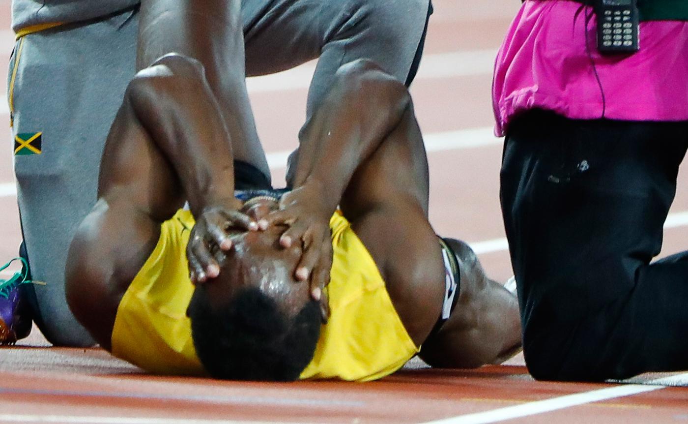 Atletismo - Campeonato Mundial de Atletismo - Final Posta Masculina 4x100 Metros - Estadio de Londres, Londres, Reino Unido – 12 de agosto, 2017. Usan Bolt de Jamaica reacciona después de sufrir una lesión. REUTERS/Lucy Nicholson