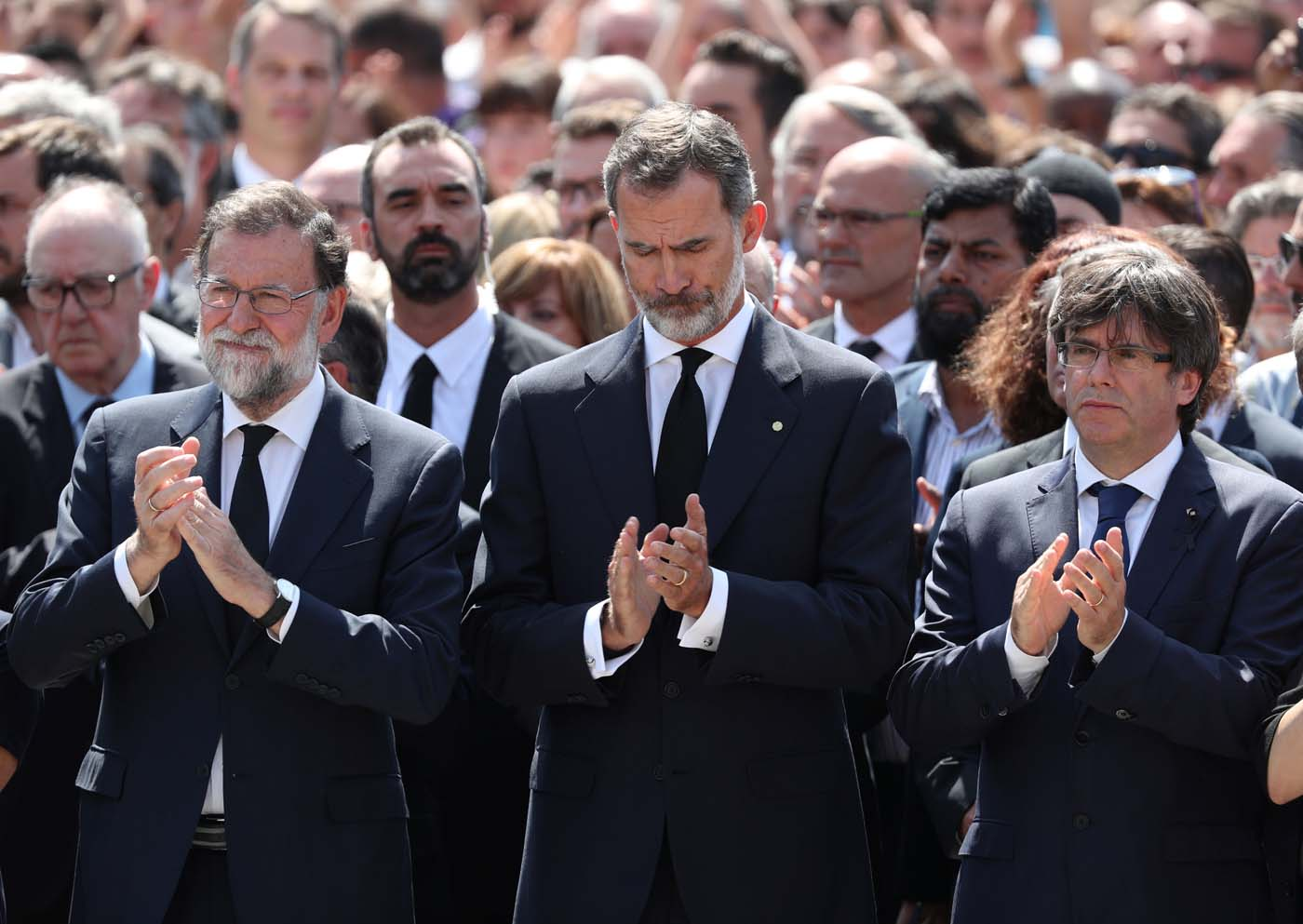 King Felipe of Spain sits between Prime Minister Mariano Rajoy and President of the Generalitat of Catalonia Carles Puigdemont as they observe a minute of silence in Placa de Catalunya, a day after a van crashed into pedestrians at Las Ramblas in Barcelona, Spain August 18, 2017. REUTERS/Sergio Perez