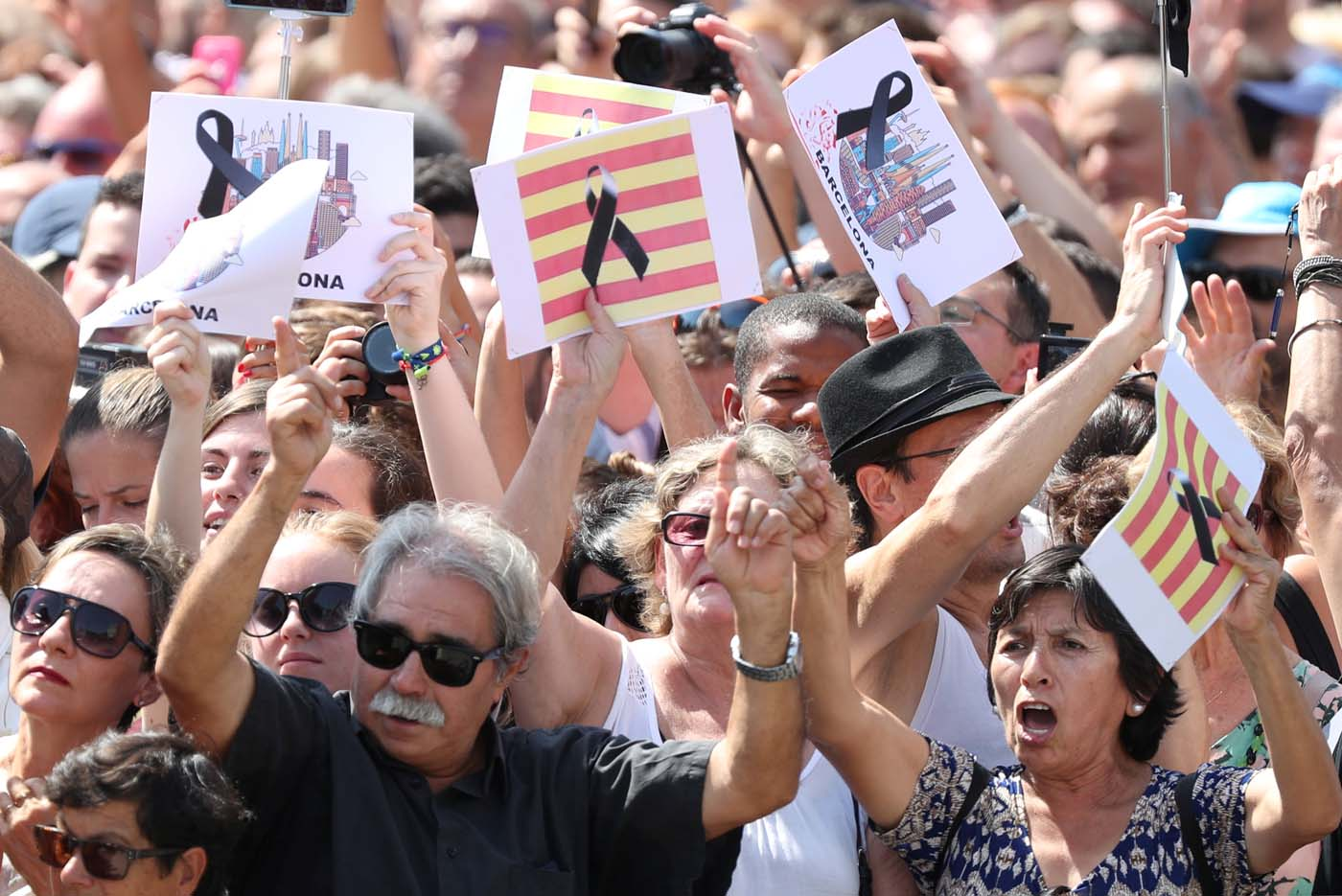 People hold banners as they observe a minute of silence in Placa de Catalunya, a day after a van crashed into pedestrians at Las Ramblas in Barcelona, Spain August 18, 2017. REUTERS/Sergio Perez