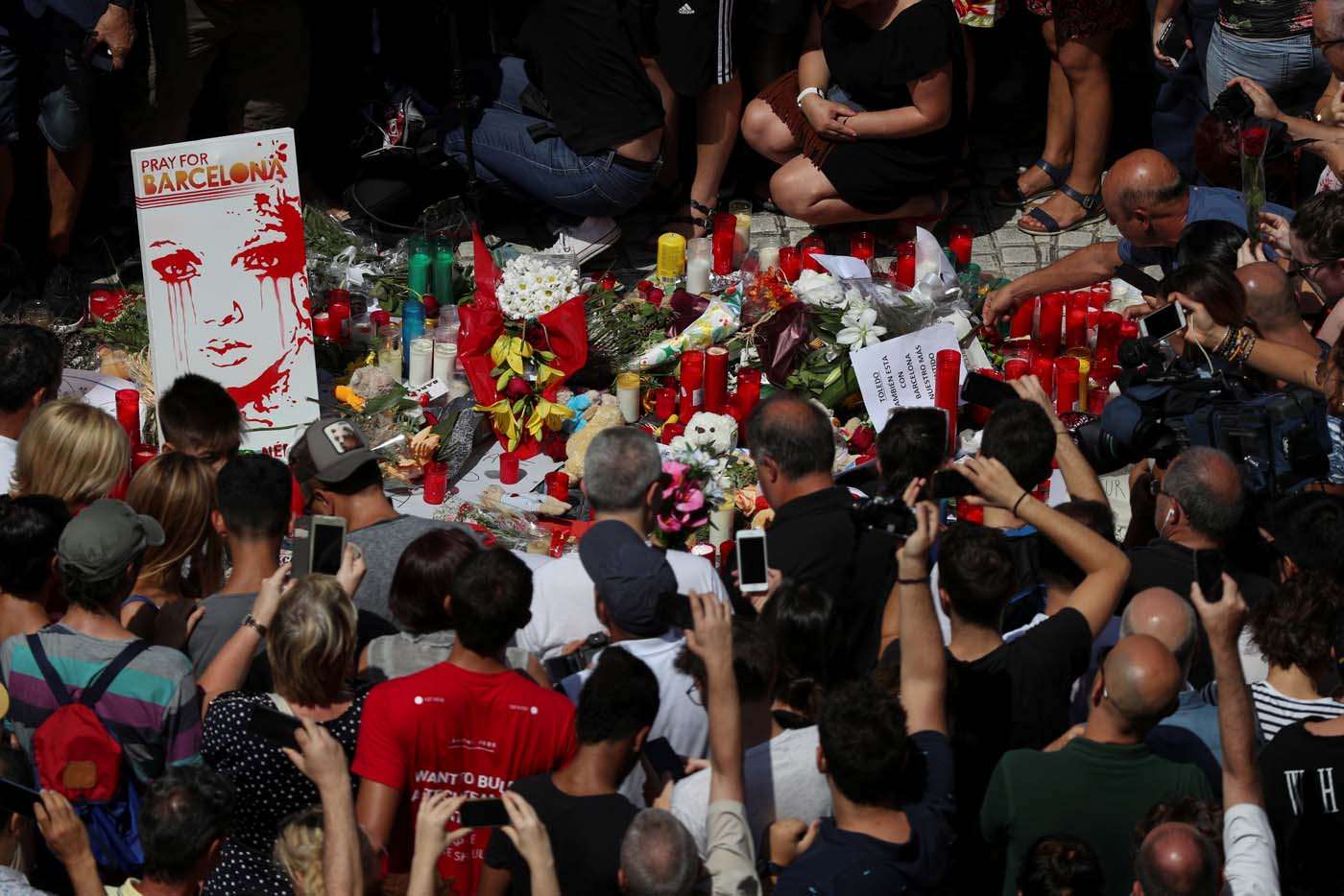 People gather around flowers and candles at Las Ramblas the day after a van crashed into pedestrians in Barcelona, Spain, August 18, 2017. REUTERS/Sergio Perez