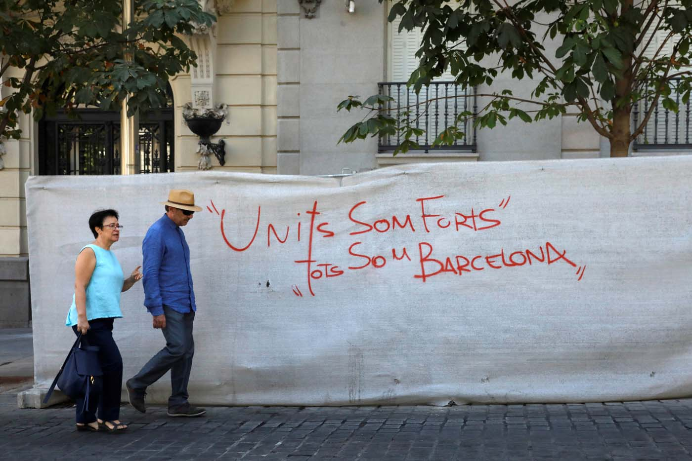 "A couple walks past a graffiti that reads ""United we are strong, we are all Barcelona"" in Madrid, Spain, August 18, 2017. REUTERS/Juan Medina"