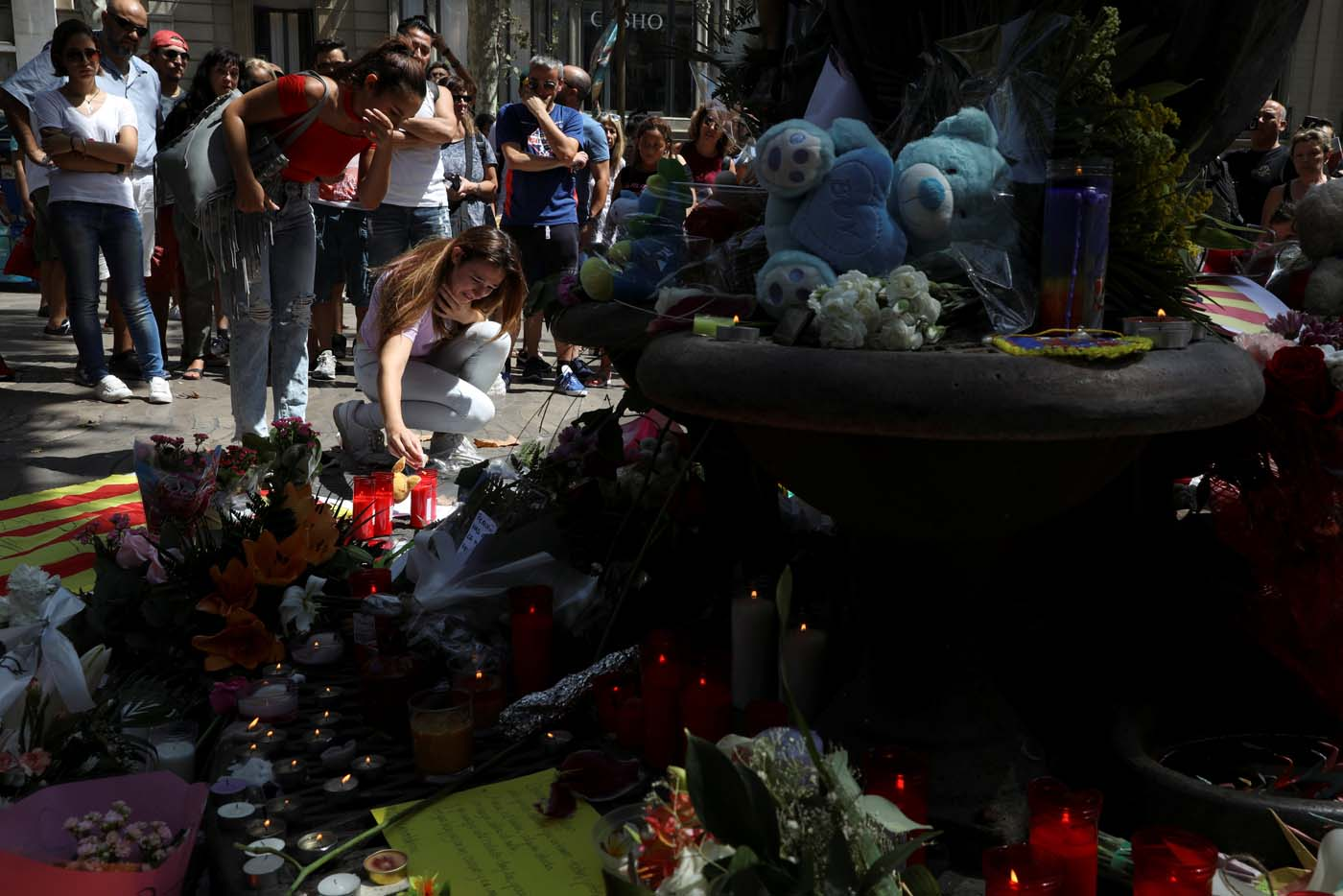 People react at an impromptu memorial a day after a van crashed into pedestrians at Las Ramblas in Barcelona, Spain August 18, 2017. REUTERS/Susana Vera