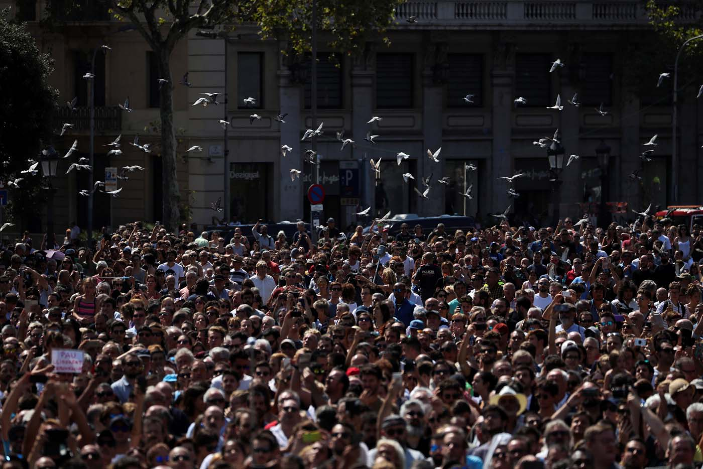 Doves fly over people gathered to observe a minute of silence at Placa de Catalunya, a day after a van crashed into pedestrians at Las Ramblas in Barcelona, Spain August 18, 2017. REUTERS/Susana Vera