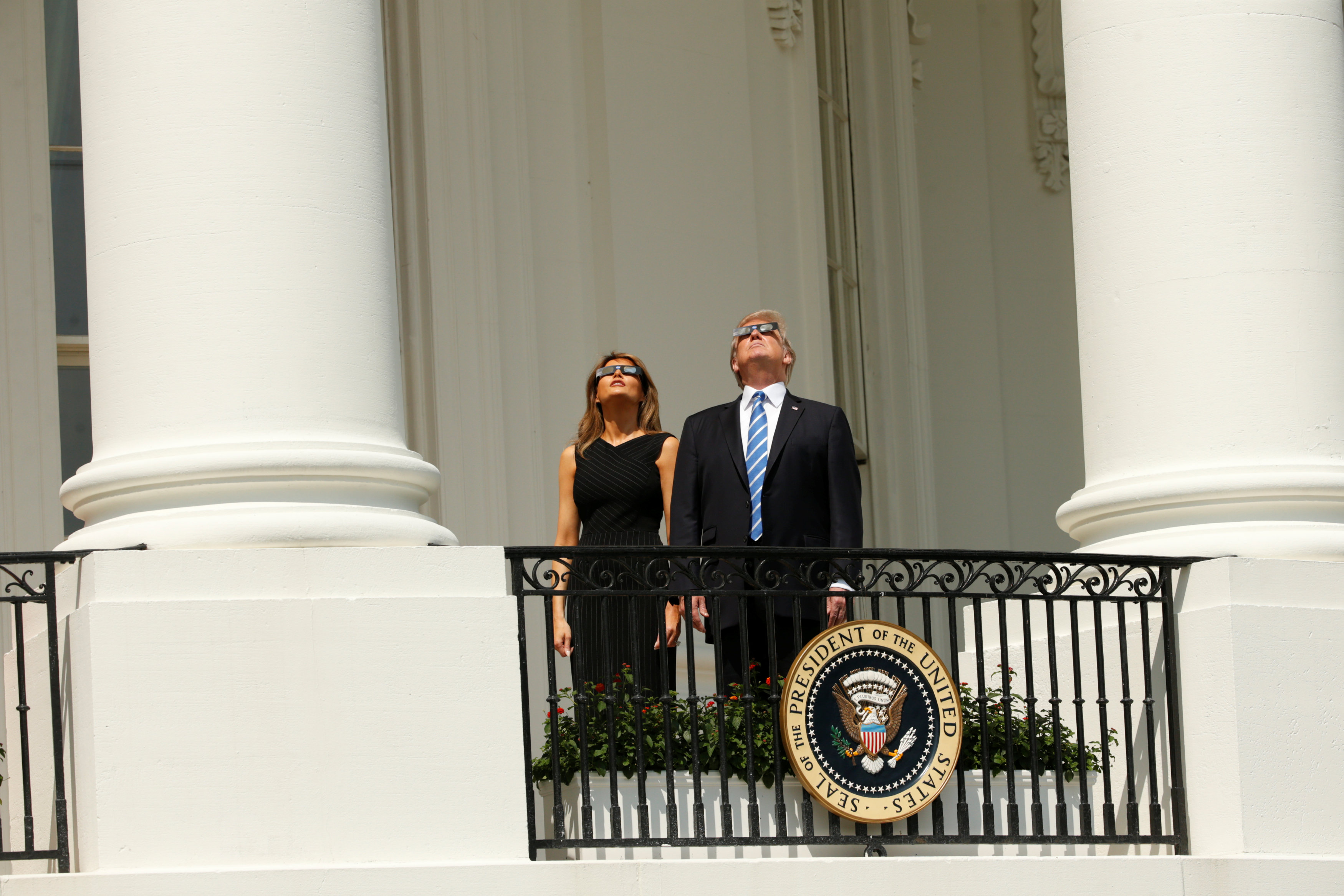 U.S. President Donald Trump watches the solar eclipse with first Lady Melania Trump from the Truman Balcony at the White House in Washington, U.S., August 21, 2017. REUTERS/Kevin Lamarque
