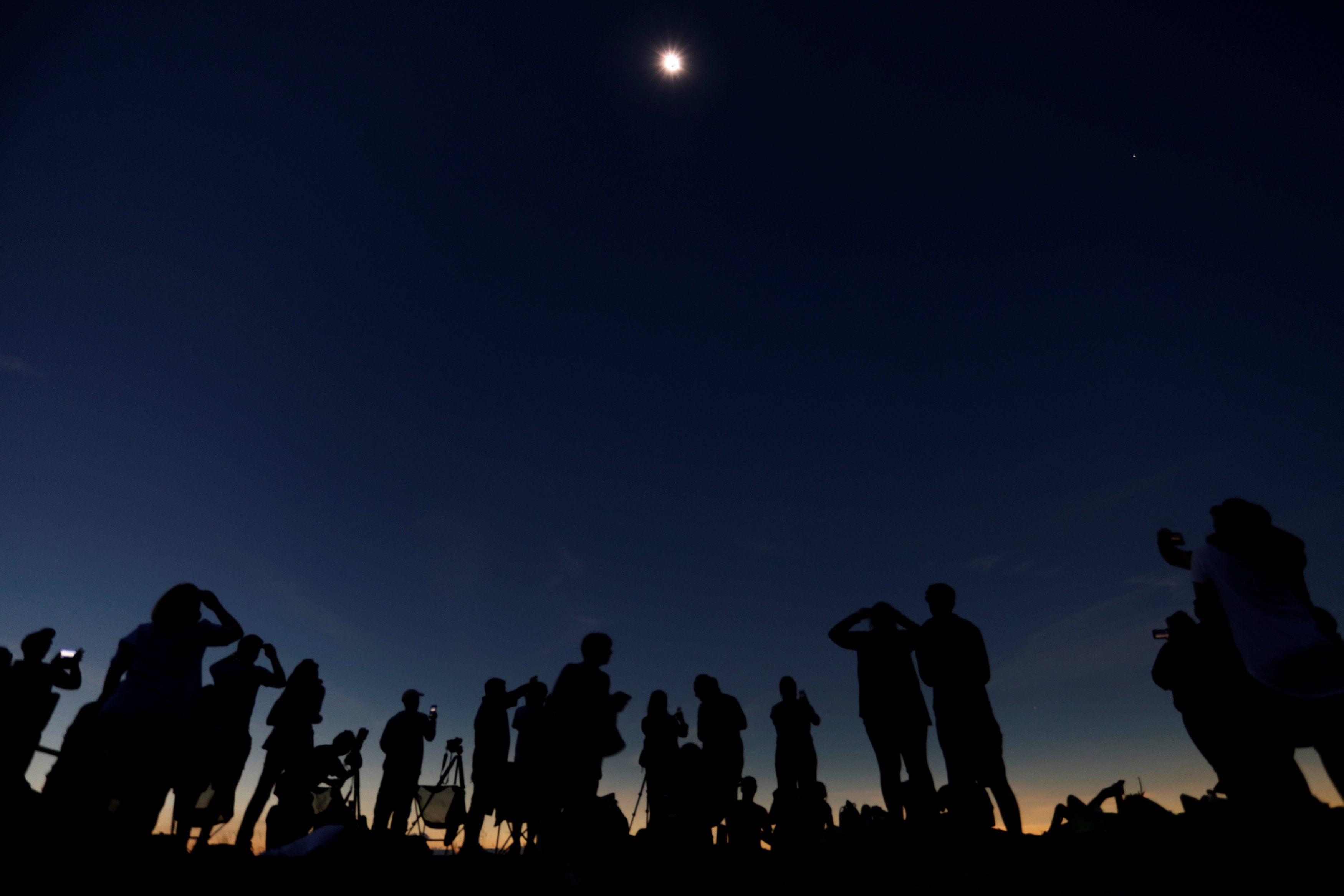 "People watch the total solar eclipse from Clingmans Dome, which at 6,643 feet (2,025m) is the highest point in the Great Smoky Mountains National Park, Tennessee, U.S. August 21, 2017. Location coordinates for this image are 35º33'24"" N, 83º29'46"" W. REUTERS/Jonathan Ernst"
