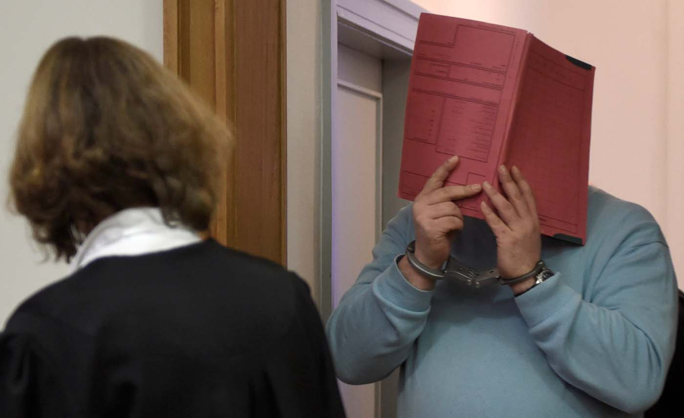 FILE PHOTO: Former nurse Niels H. (R) masks his face with a folder on his arrival in the courtroom at the regional court in Oldenburg, December 9, 2014.     REUTERS/Fabian Bimmer/File Photo