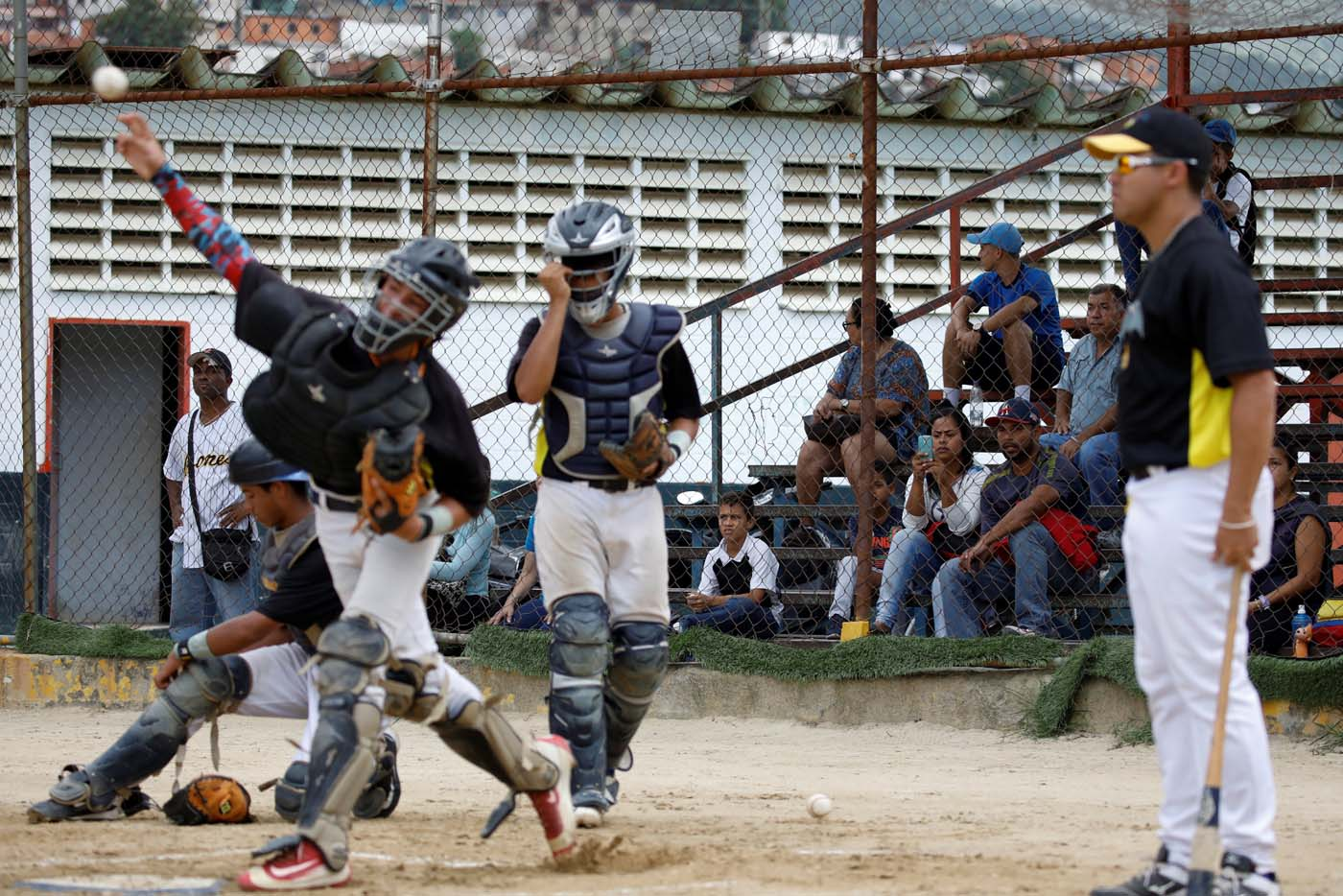 Grey Mejia (C) uses her cellphone to takes pictures to her son Rivaldo Avila (kneeling on L) and the other players, during a baseball showcase in Caracas, Venezuela August 25, 2017. Picture taken August 25, 2017. REUTERS/Carlos Garcia Rawlins
