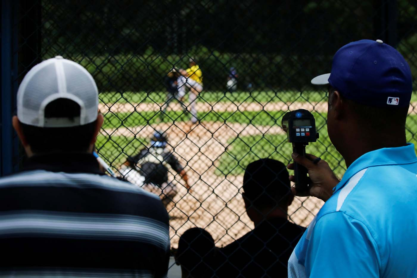 Trainers and scouts look at players during a baseball showcase in Caracas, Venezuela August 22, 2017. Picture taken August 22, 2017. REUTERS/Carlos Garcia Rawlins