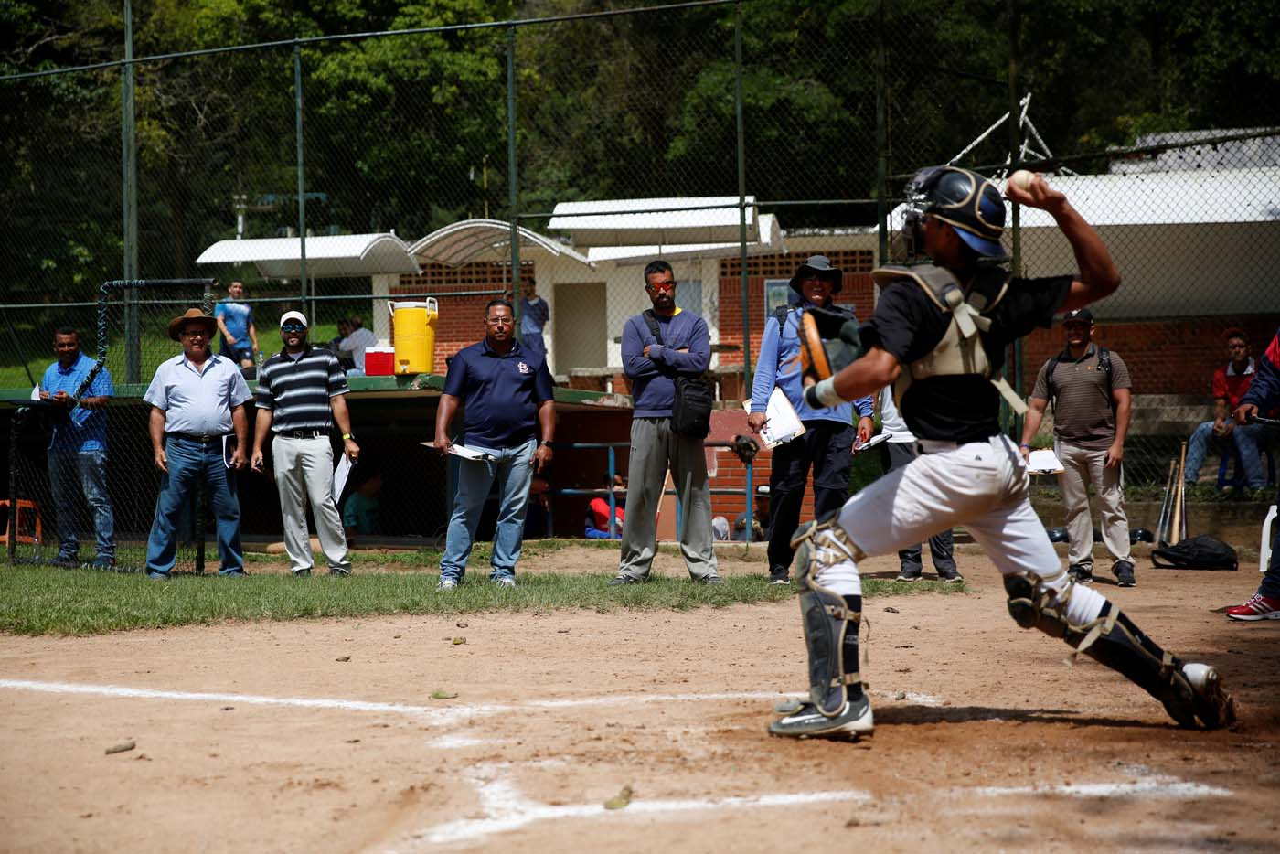 Trainers and scouts look at Rivaldo Avila (R) during a baseball showcase in Caracas, Venezuela August 22, 2017. Picture taken August 22, 2017. REUTERS/Carlos Garcia Rawlins