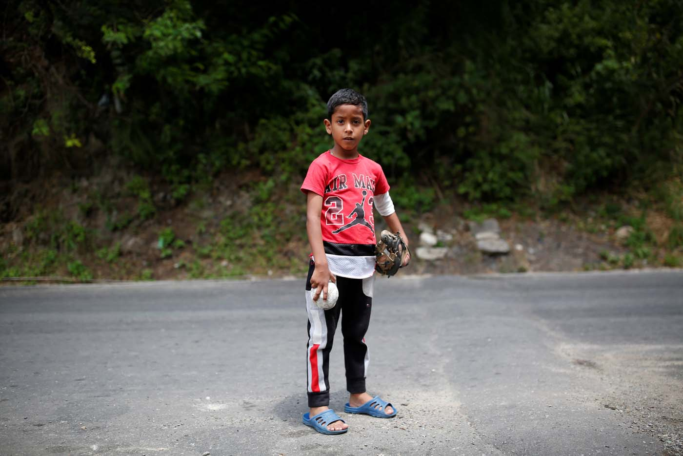 Luis Mejia, 7, poses for a picture after practice baseball on the street in Caracas, Venezuela August 29, 2017. Picture taken August 29, 2017. REUTERS/Carlos Garcia Rawlins