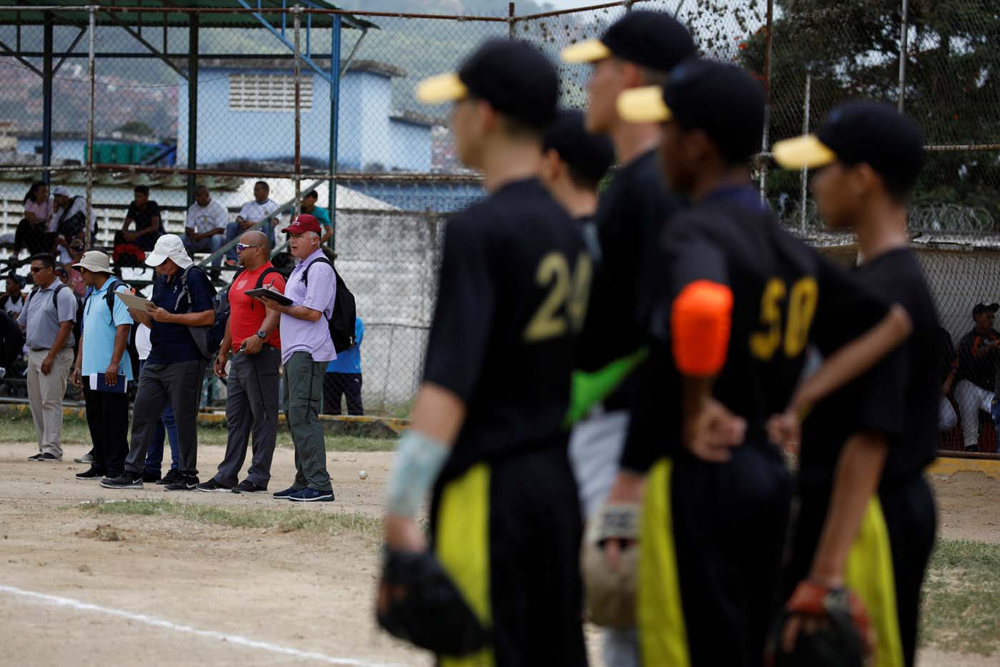 Trainers and scouts look at the players during a baseball showcase in Caracas, Venezuela August 25, 2017. Picture taken August 25, 2017. REUTERS/Carlos Garcia Rawlins