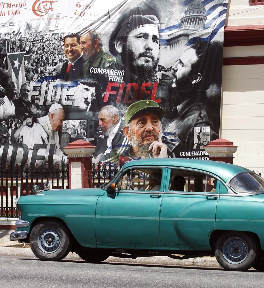 """HAB102. LA HABANA (CUBA), 13/08/2017.- Un coche clásico pasa frente a un gran cartel con diferentes imágenes del líder de la revolución cubana Fidel Castro, en el día de su 91 cumpleaños, hoy, domingo 13 de agosto del 2017, en La Habana (Cuba). Cuba recuerda hoy el 91 aniversario del natalicio del líder de la revolución, Fidel Castro, el primero tras su fallecimiento hace nueve meses, que se celebra este domingo con múltiples actos y una amplia cobertura en los medios estatales de la isla que resaltan el legado del """"invicto y eterno Comandante"""". EFE/Ernesto Mastrascusa"""