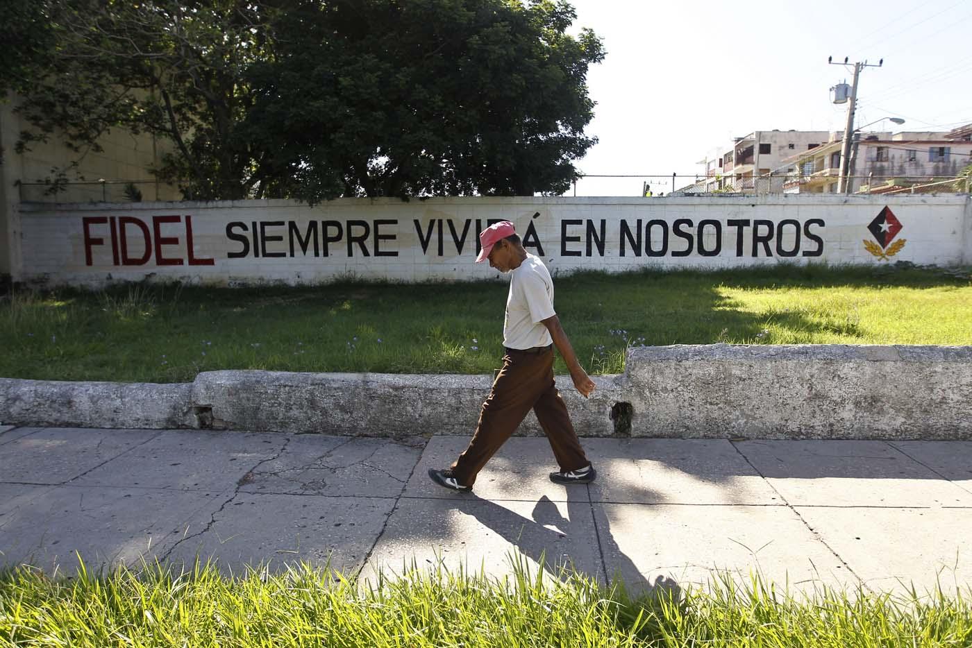 """HAB104. LA HABANA (CUBA), 13/08/2017.- Un hombre pasa junto a un cartel pintado en un muro, referente al líder de la revolución cubana Fidel Castro, en el día de su 91 cumpleaños, hoy, domingo 13 de agosto del 2017, en La Habana (Cuba). Cuba recuerda hoy el 91 aniversario del natalicio del líder de la revolución, Fidel Castro, el primero tras su fallecimiento hace nueve meses, que se celebra este domingo con múltiples actos y una amplia cobertura en los medios estatales de la isla que resaltan el legado del """"invicto y eterno Comandante"""". EFE/Ernesto Mastrascusa"""