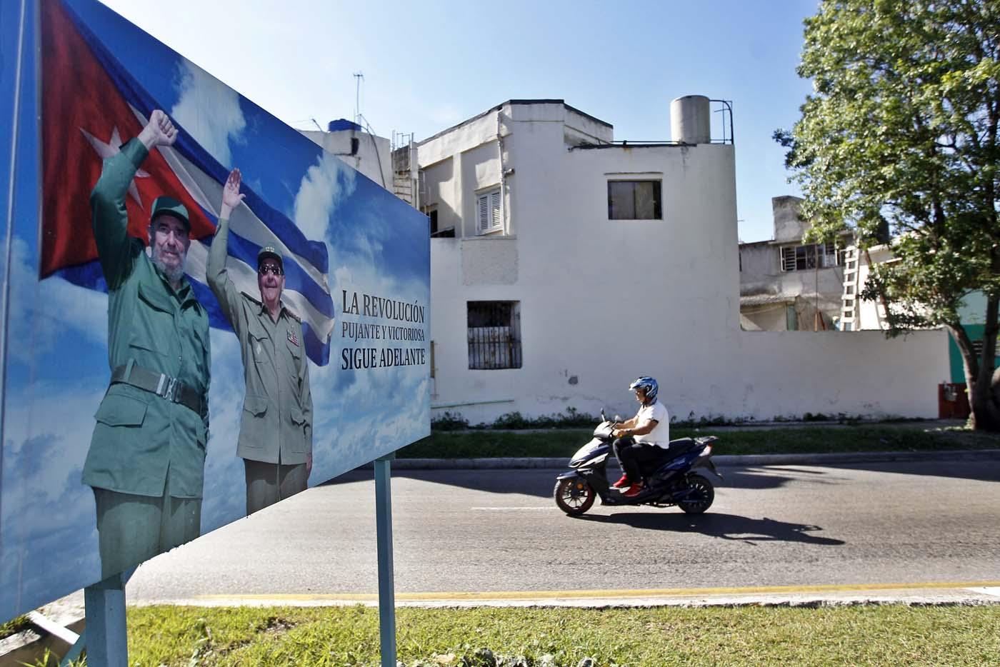 """HAB105. LA HABANA (CUBA), 13/08/2017.- Un hombre en moto pasa junto a un cartel con la imagen del líder de la revolución cubana Fidel Castro, en el día de su 91 cumpleaños, hoy, domingo 13 de agosto del 2017, en La Habana (Cuba). Cuba recuerda hoy el 91 aniversario del natalicio del líder de la revolución, Fidel Castro, el primero tras su fallecimiento hace nueve meses, que se celebra este domingo con múltiples actos y una amplia cobertura en los medios estatales de la isla que resaltan el legado del """"invicto y eterno Comandante"""". EFE/Ernesto Mastrascusa"""