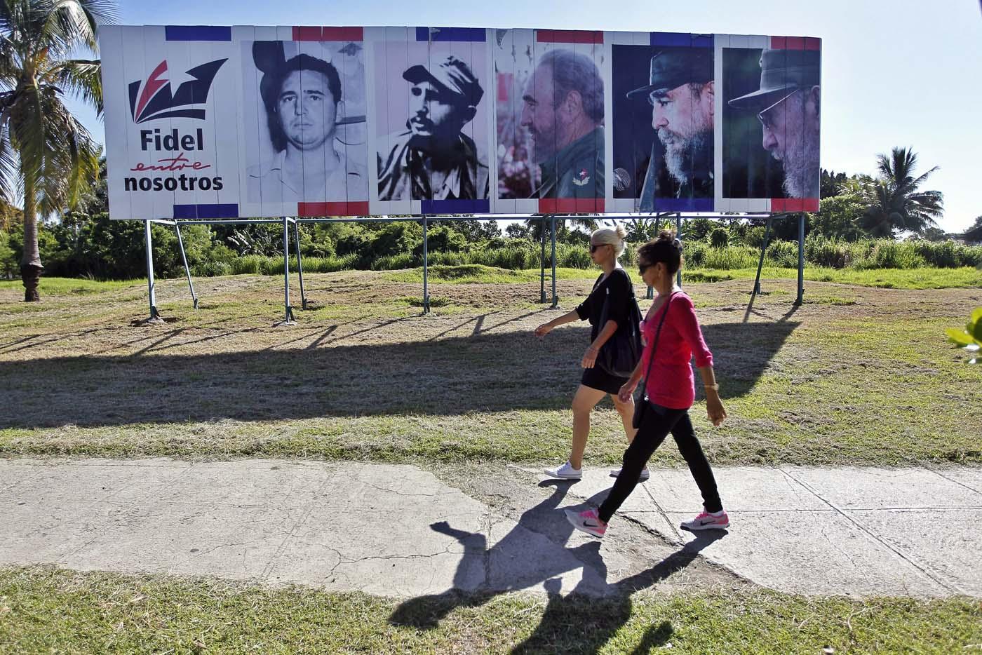 """HAB106. LA HABANA (CUBA), 13/08/2017.- Dos mujeres caminan junto a un cartel con la imagen del líder de la revolución cubana Fidel Castro, en el día de su 91 cumpleaños, hoy, domingo 13 de agosto del 2017, en La Habana (Cuba). Cuba recuerda hoy el 91 aniversario del natalicio del líder de la revolución, Fidel Castro, el primero tras su fallecimiento hace nueve meses, que se celebra este domingo con múltiples actos y una amplia cobertura en los medios estatales de la isla que resaltan el legado del """"invicto y eterno Comandante"""". EFE/Ernesto Mastrascusa"""