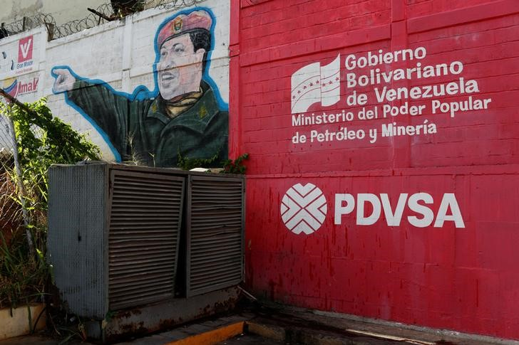 The logo of the Venezuelan state oil company PDVSA is seen next to a mural depicting Venezuela's late President Hugo Chavez at a gas station in Caracas, Venezuela March 2, 2017. Picture taken March 2, 2017. To match Insight VENEZUELA-INDIA/OIL REUTERS/Carlos Garcia Rawlins