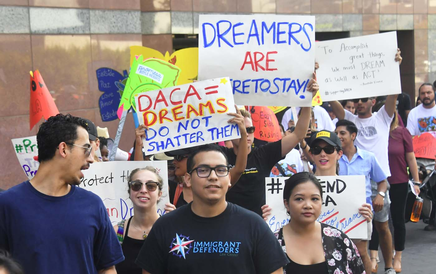 Young immigrants and supporters walk holding signs during a rally in support of Deferred Action for Childhood Arrivals (DACA) in Los Angeles, California on September 1, 2017. A decision is expected in coming days on whether US President Trump will end the program by his predecessor, former President Obama, on DACA which has protected some 800,000 undocumented immigrants, also known as Dreamers, since 2012. / AFP PHOTO / FREDERIC J. BROWN