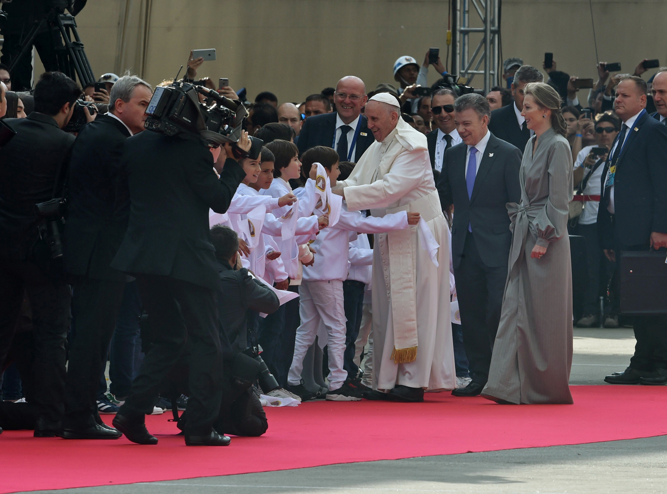 "Pope Francis greets children after being welcomed by Colombia President Juan Manuel Santos and his wife Maria Clemencia (R) upon landing in Bogota on September 6, 2017.  Pope Francis arrived in Colombia for a five-day tour to plead for a ""stable and lasting"" peace in a divided country just emerging from a 50-year war that claimed hundreds of thousands of lives. / AFP PHOTO / Rodrigo ARANGUA"