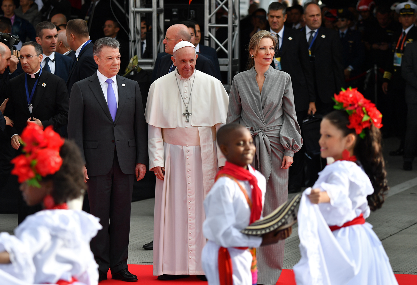 "Pope Francis (C) is welcomed by Colombia President Juan Manuel Santos (L) and his wife Maria Clemencia upon landing in Bogota on September 6, 2017.  Pope Francis arrived in Colombia for a five-day tour to plead for a ""stable and lasting"" peace in a divided country just emerging from a 50-year war that claimed hundreds of thousands of lives. / AFP PHOTO / Alberto PIZZOLI"