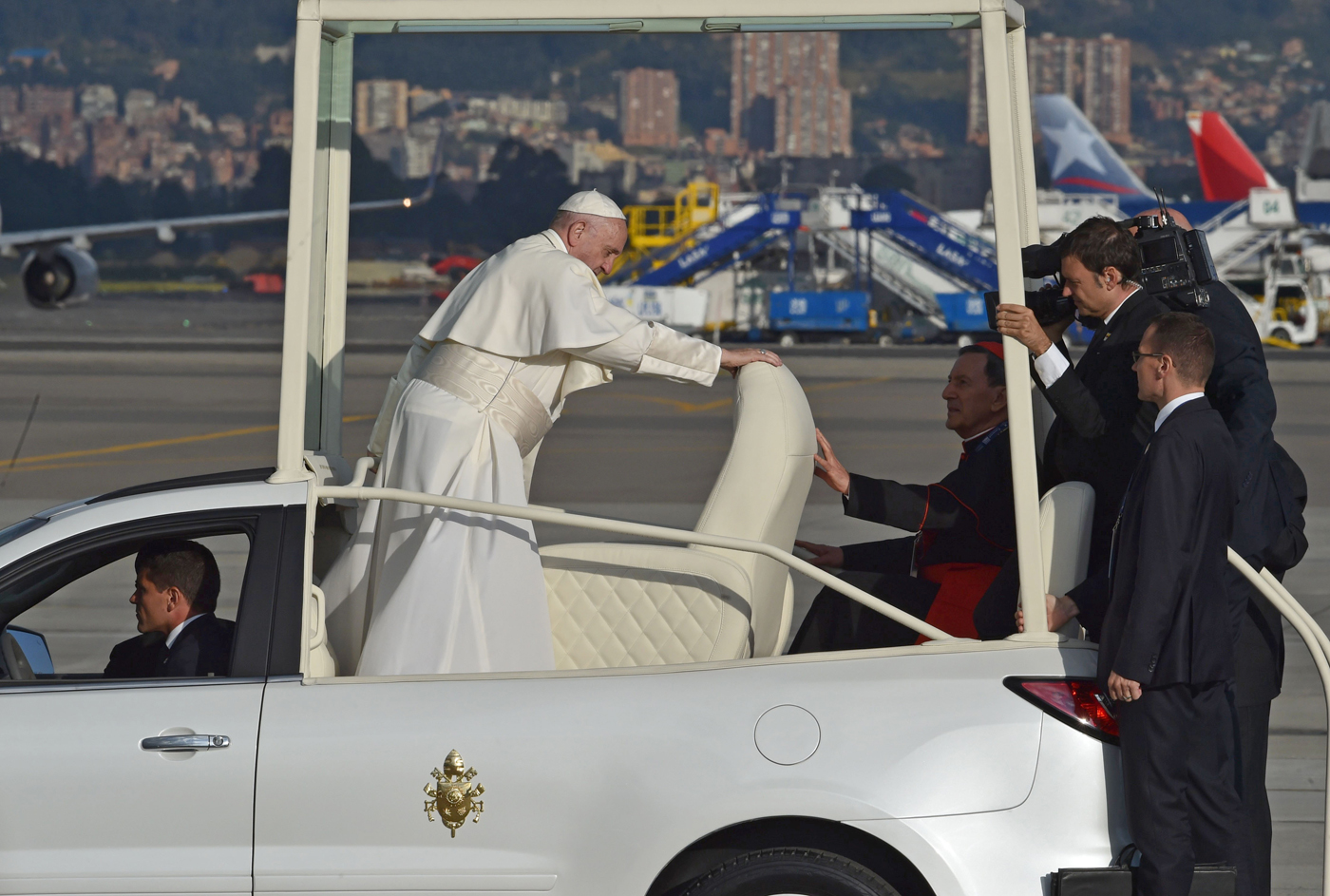 "Pope Francis (C) adjusts his sit after getting onto the Popemobile upon his arrival to Bogota on September 6, 2017. Pope Francis set off for Colombia on Wednesday for a five-day tour to plead for a ""stable and lasting"" peace in a divided country just emerging from a 50-year war that claimed hundreds of thousands of lives. / AFP PHOTO / RODRIGO ARANGUA"