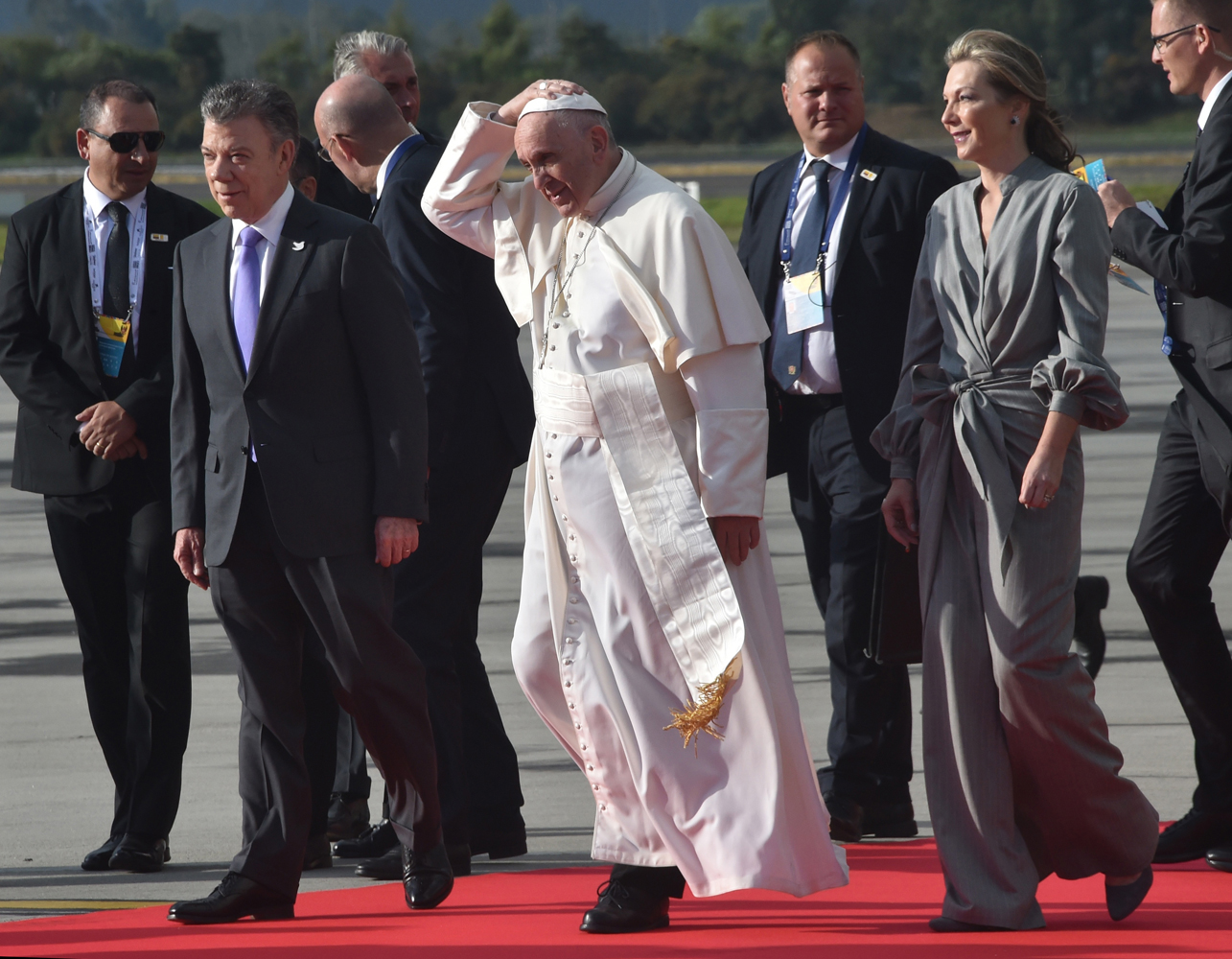"Pope Francis (C) walks flanked by Colombian President Juan Manuel Santos and his wife Maria Clemencia Rodriguez (R), upon his arrival to Bogota on September 6, 2017. Pope Francis arrived in Colombia for a five-day tour to plead for a ""stable and lasting"" peace in a divided country just emerging from a 50-year war that claimed hundreds of thousands of lives. / AFP PHOTO / RODRIGO ARANGUA"