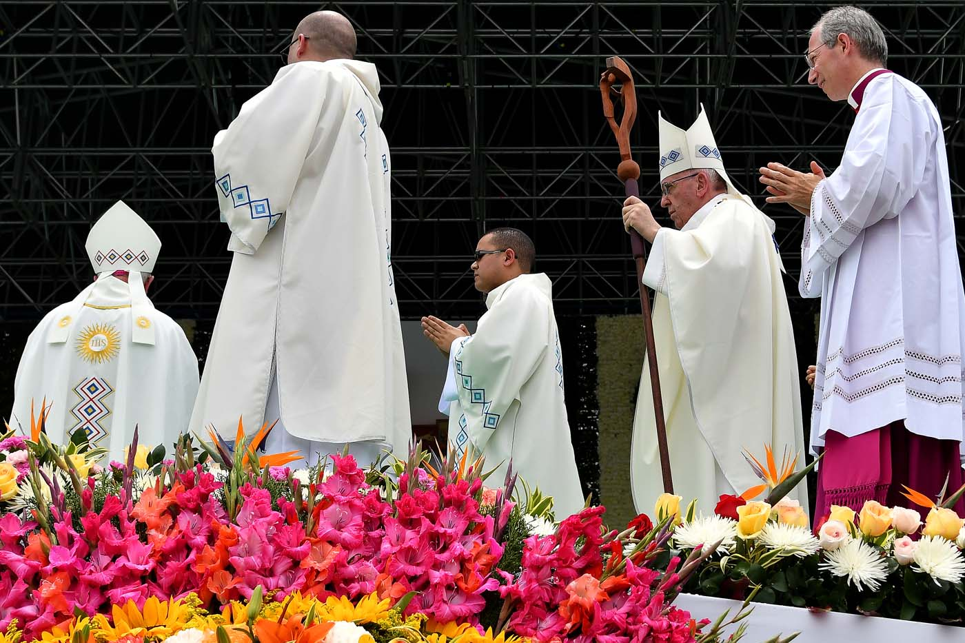 Pope Francis (2-R) walks to the altar to give mass at the Enrique Olaya Herrera airport in Medellin, Colombia, on September 9, 2017. Pope Francis visits the Colombian city of Medellin, former stronghold of the late drug baron Pablo Escobar, on the fourth day of a papal tour to promote peace. / AFP PHOTO / Alberto PIZZOLI