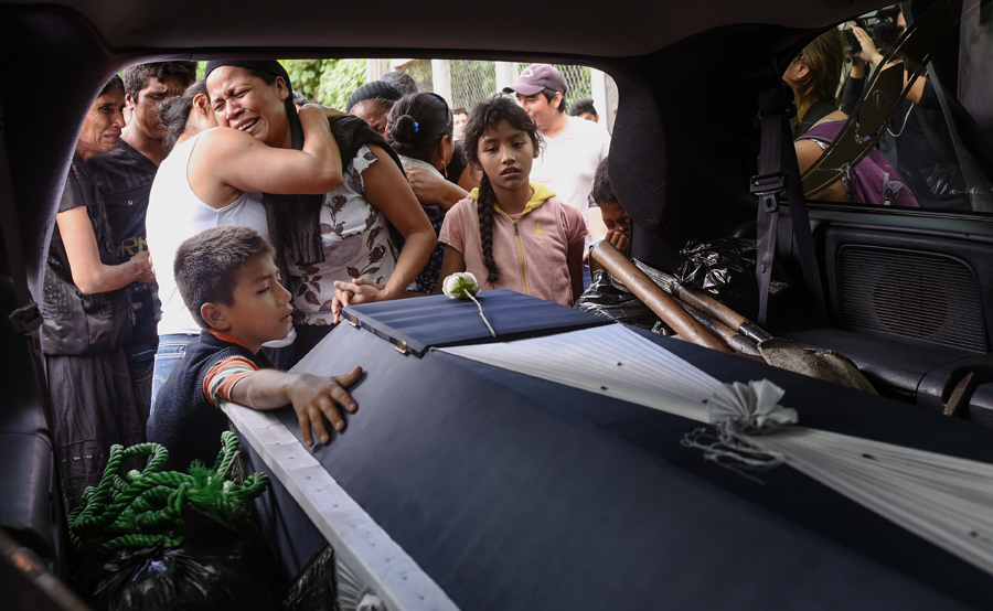 Relatives of late policeman Juan Jimenez mourn him during a funeral of victims of the 8.2-magnitude earthquake that hit Mexico's Pacific coast, in Juchitan de Zaragoza, state of Oaxaca, Mexico on September 10, 2017. Families camped out Sunday in southern Mexico as rescuers dug for bodies amid warnings that the death toll of 65 from the country's biggest earthquake in a century could rise. / AFP PHOTO / VICTORIA RAZO