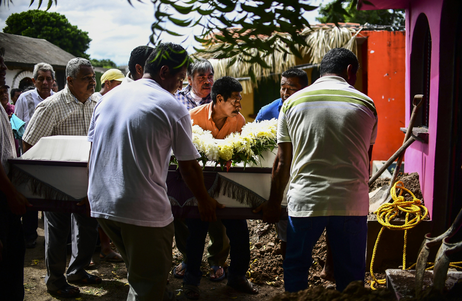 Relatives and friends accompany to the cemetery the remains of a victim of Thursday night's 8.2-magnitude quake, in Juchitan, Oaxaca, Mexico, on September 10, 2017. Rescuers pulled bodies from the rubble and grieving families carried coffins through the streets Saturday after Mexico's biggest earthquake in a century killed 65 people. / AFP PHOTO / RONALDO SCHEMIDT