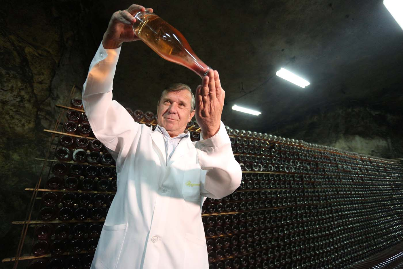 "Winemaker Rafail Nasyrov holds a bottle of wine in the ""Artwinery"" winery firm in the eastern Ukrainian city of Bakhmut on July 12, 2017. The winery is located in a government-held town just two dozen kilometres (15 miles) from the frontline in Ukraine's low-level war, where the army and Russian-backed rebels continue to lob deadly artillery barrages at each other. The town spent around a month under rebel control in 2014, and in 2015 the frontline was so close that the town came under rebel shelling. But despite more than three years of fighting that has claimed some 10,000 lives, Nasyrov's employer, Artwinery, has never stopped production. / AFP PHOTO / Aleksey FILIPPOV"
