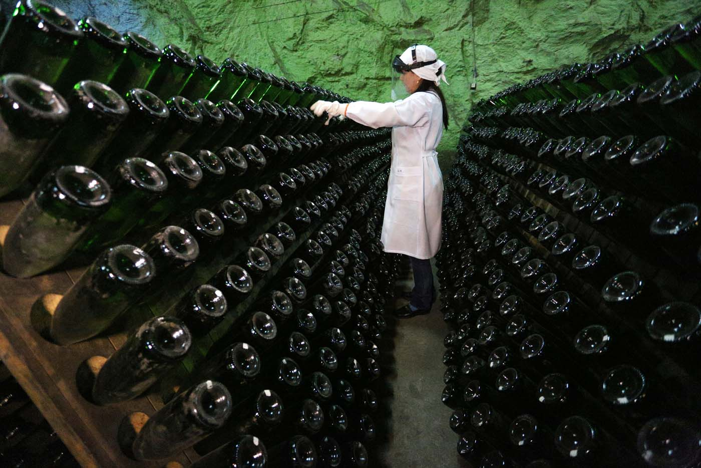 "An employee turns bottles in the ""Artwinery"" winery firm in the eastern Ukrainian city of Bakhmut on July 12, 2017. The winery is located in a government-held town just two dozen kilometres (15 miles) from the frontline in Ukraine's low-level war, where the army and Russian-backed rebels continue to lob deadly artillery barrages at each other. The town spent around a month under rebel control in 2014, and in 2015 the frontline was so close that the town came under rebel shelling. But despite more than three years of fighting that has claimed some 10,000 lives, Nasyrov's employer, Artwinery, has never stopped production. / AFP PHOTO / Aleksey FILIPPOV"