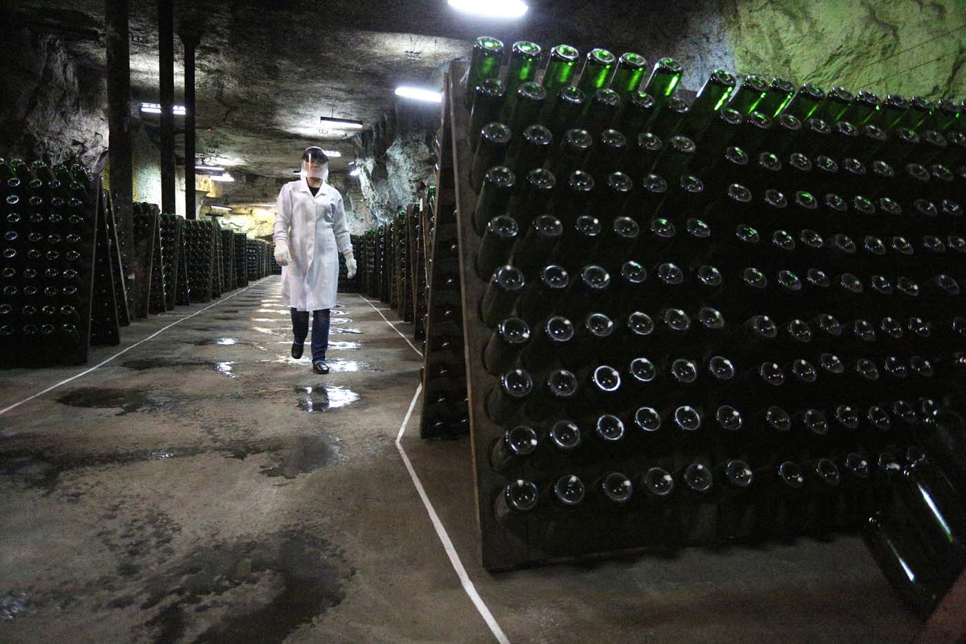 "An employee walks past bottles in the ""Artwinery"" winery firm in the eastern Ukrainian city of Bakhmut on July 12, 2017. The winery is located in a government-held town just two dozen kilometres (15 miles) from the frontline in Ukraine's low-level war, where the army and Russian-backed rebels continue to lob deadly artillery barrages at each other. The town spent around a month under rebel control in 2014, and in 2015 the frontline was so close that the town came under rebel shelling. But despite more than three years of fighting that has claimed some 10,000 lives, Nasyrov's employer, Artwinery, has never stopped production. / AFP PHOTO / Aleksey FILIPPOV"