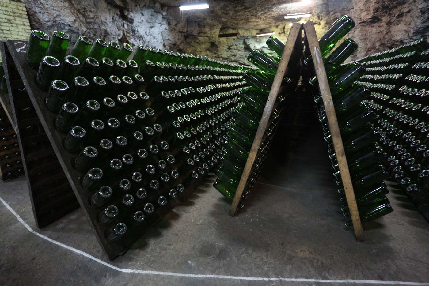 "A picture taken on July 12, 2017 shows bottles of wine in the ""Artwinery"" winery firm in the eastern Ukrainian city of Bakhmut. The winery is located in a government-held town just two dozen kilometres (15 miles) from the frontline in Ukraine's low-level war, where the army and Russian-backed rebels continue to lob deadly artillery barrages at each other. The town spent around a month under rebel control in 2014, and in 2015 the frontline was so close that the town came under rebel shelling. But despite more than three years of fighting that has claimed some 10,000 lives, Nasyrov's employer, Artwinery, has never stopped production. / AFP PHOTO / Aleksey FILIPPOV"
