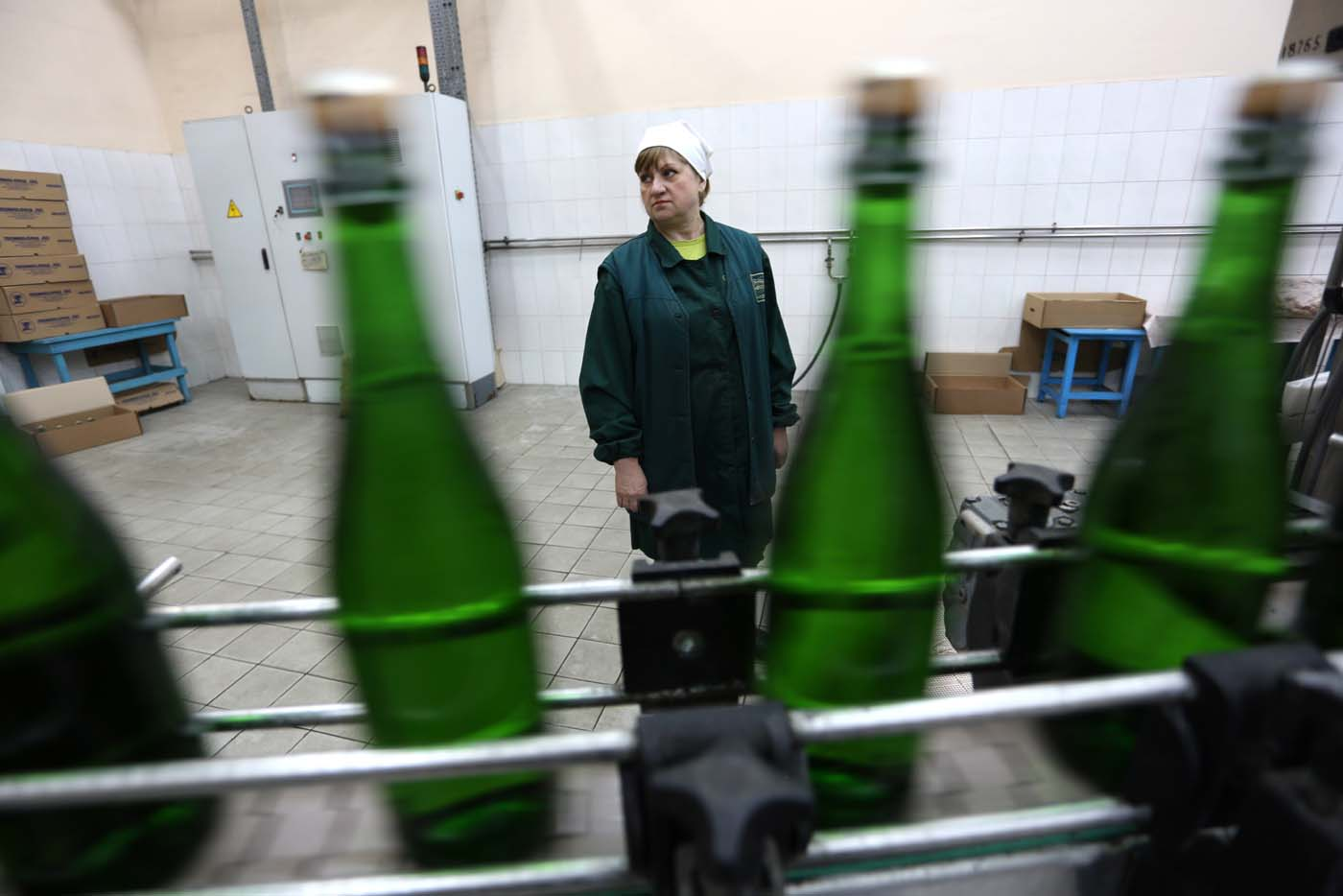 "An employee stands as she works on the production line in the ""Artwinery"" winery firm in the eastern Ukrainian city of Bakhmut on July 12, 2017. The winery is located in a government-held town just two dozen kilometres (15 miles) from the frontline in Ukraine's low-level war, where the army and Russian-backed rebels continue to lob deadly artillery barrages at each other. The town spent around a month under rebel control in 2014, and in 2015 the frontline was so close that the town came under rebel shelling. But despite more than three years of fighting that has claimed some 10,000 lives, Nasyrov's employer, Artwinery, has never stopped production. / AFP PHOTO / Aleksey FILIPPOV"