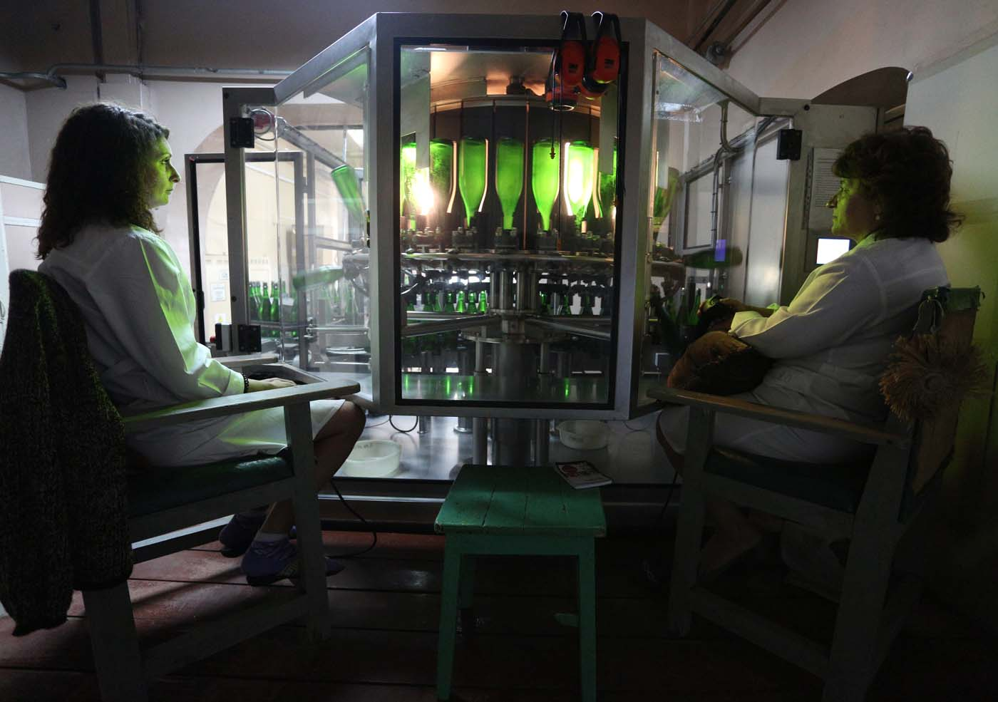 "Employees work on the production line in the ""Artwinery"" winery firm in the eastern Ukrainian city of Bakhmut on July 12, 2017. The winery is located in a government-held town just two dozen kilometres (15 miles) from the frontline in Ukraine's low-level war, where the army and Russian-backed rebels continue to lob deadly artillery barrages at each other. The town spent around a month under rebel control in 2014, and in 2015 the frontline was so close that the town came under rebel shelling. But despite more than three years of fighting that has claimed some 10,000 lives, Nasyrov's employer, Artwinery, has never stopped production. / AFP PHOTO / Aleksey FILIPPOV"
