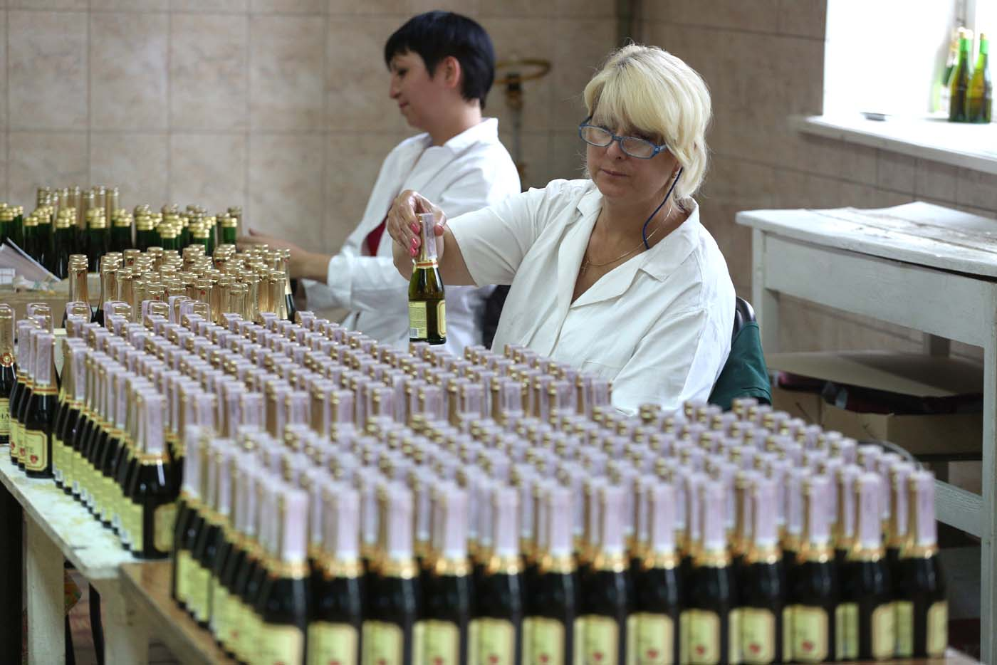 "An employee checks bottles as she works on the production line in the ""Artwinery"" winery firm in the eastern Ukrainian city of Bakhmut on July 12, 2017. The winery is located in a government-held town just two dozen kilometres (15 miles) from the frontline in Ukraine's low-level war, where the army and Russian-backed rebels continue to lob deadly artillery barrages at each other. The town spent around a month under rebel control in 2014, and in 2015 the frontline was so close that the town came under rebel shelling. But despite more than three years of fighting that has claimed some 10,000 lives, Nasyrov's employer, Artwinery, has never stopped production. / AFP PHOTO / Aleksey FILIPPOV"