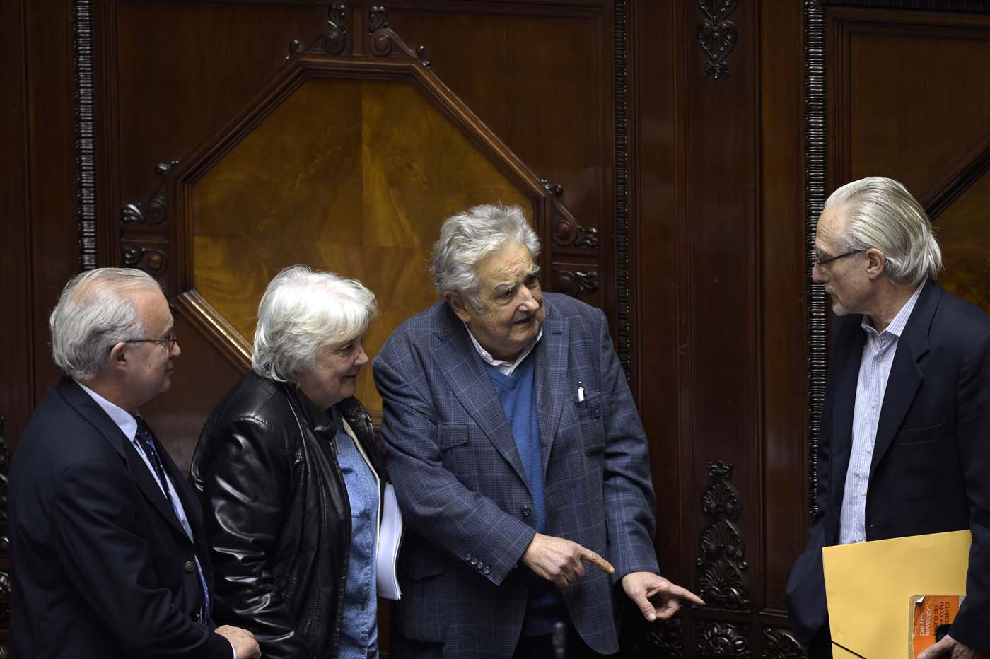 Uruguay's new vice-president Lucia Topolansky (2nd-L), accompanied by her husband, senator and former president Jode Mujica (2nd-R), talk with fellow lawmakers after her swearing-in ceremony in Montevideo, on September 13, 2017. Topolansky replaces Raul Sendic, who resigned on Saturday over allegations he used public money for personal shopping. / AFP PHOTO / MIGUEL ROJO