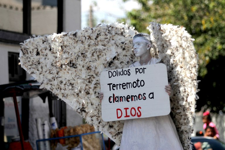 A member of Christian church Salmo 100 dressed as an angel shows a message addressed to the victims of the last earthquake in Mexico City, in front of drivers crossing the Cordova-Americas International Bridge between Ciudad Juarez, Chihuahua state and El Paso, Texas on September 23, 2017 in Ciudad Juárez, Chihuahua, Mexico. / AFP PHOTO / HÉRIKA MARTÍNEZ