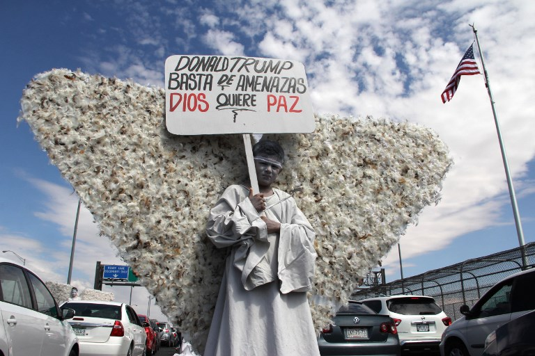"A member of Christian church Salmo 100 dressed as an angel shows a placard addressed to U.S. President Donald Trump that reads ""Donald Trump - Enough of Threats - God Wants Peace"" in front of the drivers crossing the Cordova-Americas International Bridge between Ciudad Juarez, Chihuahua state and El Paso, Texas on September 23, 2017 in Ciudad Juárez, Chihuahua, Mexico. / AFP PHOTO / HÉRIKA MARTÍNEZ"