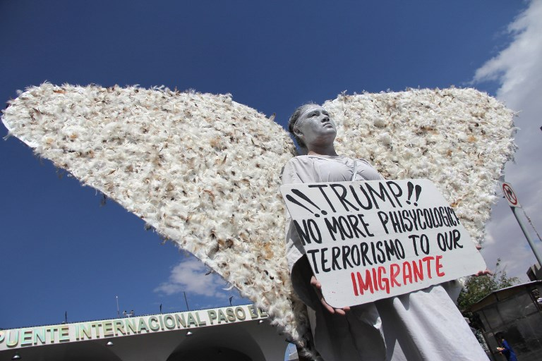 A member of Christian church Salmo 100 dressed as an angel shows a placard addressed to U.S. President Donald Trump in front of drivers crossing the Cordova-Americas International Bridge between Ciudad Juarez, Chihuahua state and El Paso, Texas on September 23, 2017 in Ciudad Juárez, Chihuahua, Mexico. / AFP PHOTO / HÉRIKA MARTÍNEZ