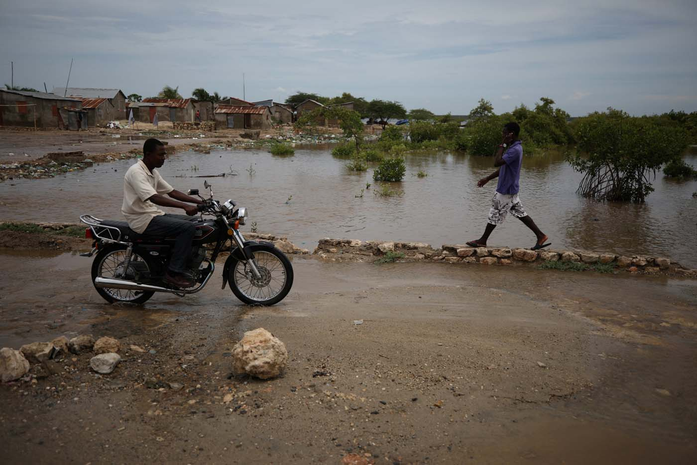 People pass next to a flooded area after hurricane Irma in Fort Liberte, Haiti September 8, 2017. REUTERS/Andres Martinez Casares