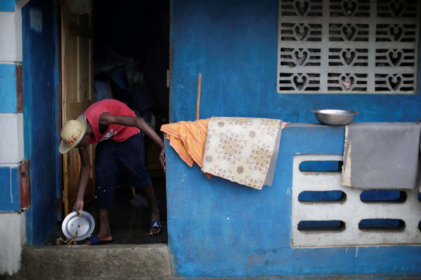 A man uses a metal plate to remove water from his house in a flooded area after hurricane Irma in Fort Liberte, Haiti September 8, 2017. REUTERS/Andres Martinez Casares