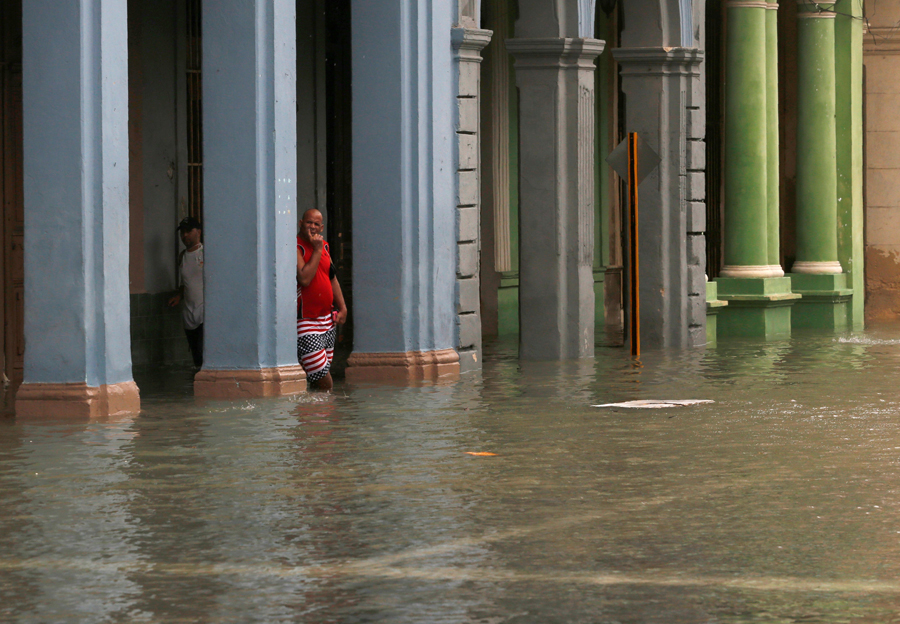 A man leans on a pillar in a flooded street after the passing of Hurricane Irma, in Havana, Cuba, September 10, 2017. REUTERS/Stringer NO SALES. NO ARCHIVES