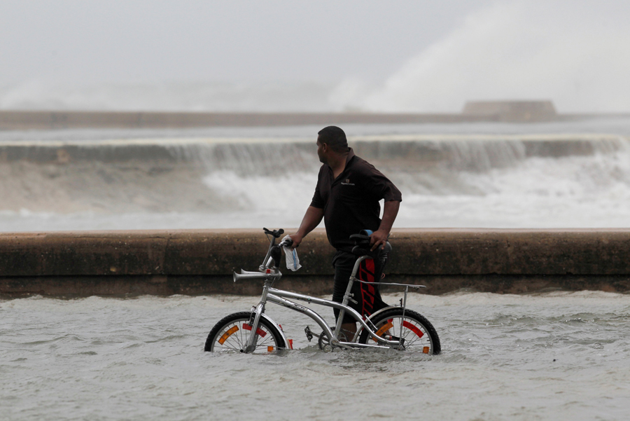 A man pushes his bike through a flooded street after the passing of Hurricane Irma, in Havana, Cuba, September 10, 2017. REUTERS/Stringer NO SALES. NO ARCHIVES