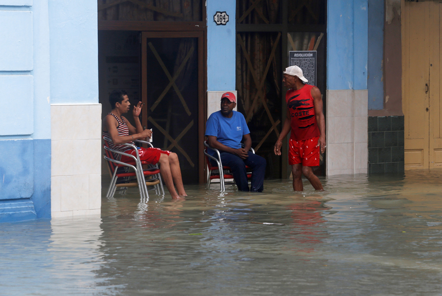 People sit in a flooded street, after the passing of Hurricane Irma, in Havana, Cuba, September 10, 2017. REUTERS/Stringer NO SALES. NO ARCHIVES