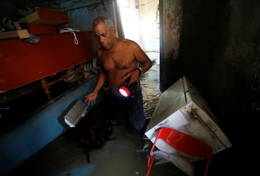 A man wades through the water in his flooded home after the passing of Hurricane Irma in Havana, Cuba, September 10, 2017. REUTERS/Stringer NO SALES. NO ARCHIVES