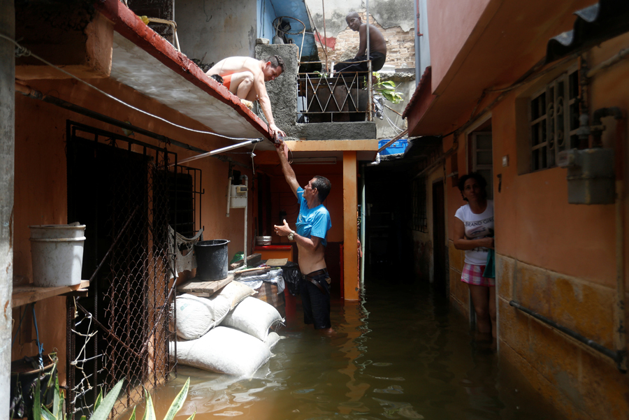A man passes a drink to a neighbour while standing in the flooded passage of a block of flats, after the passing of Hurricane Irma, in Havana, Cuba September 10, 2017. REUTERS/Stringer NO SALES. NO ARCHIVES